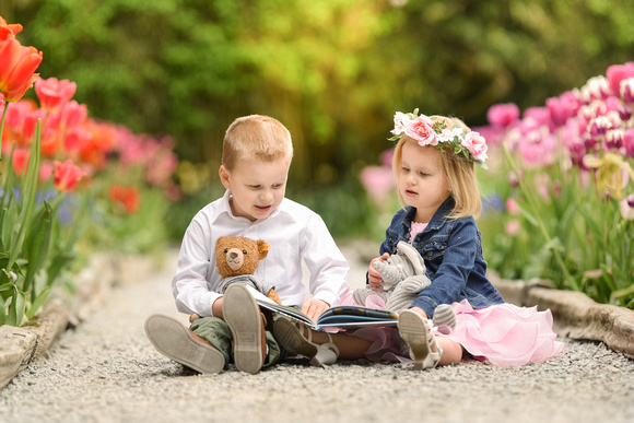 children reading a storybook with their stuffed animals
